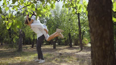 時代遅れの : Happy young man and woman having fun together in the park or garden. The guy spinning around with the girl on his back. Leisure outdoors, connecting with nature, enjoying sunny summer day