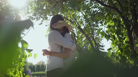 時代遅れの : Happy young couple hugging in the park or garden. Leisure outdoors, connecting with nature, enjoying sunny day.