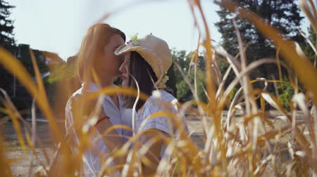 時代遅れの : Happy couple hugging behind yellow grass. Young handsome man and woman in straw hat spending time together in the park or garden. Love concept.