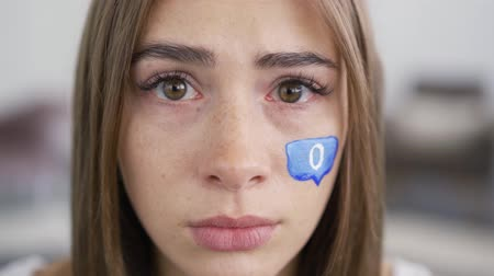 distraído : Close-up portrait of a sad crying young woman looking at the camera. Blue message box with zero painted on the girls face. Social media concept. Lack of attention, gadget addiction