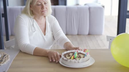 tartufo : Sad unhappy mature woman sitting at the table in front of small birthday cake in emlpy room then stands up and walking away. Birthday celebration concept. Sadness, loneliness