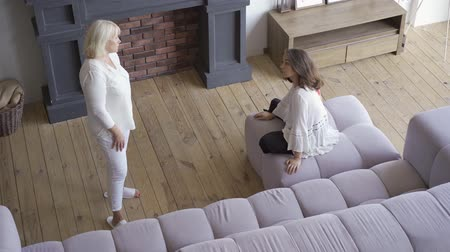 woede : Young woman arguing with her mother while sitting on the sofa in large living room. Difficult family relationship, misunderstanding between different generations Stockvideo