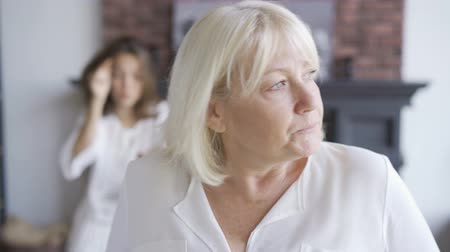 expressing negativity : Portrait of nervous mature woman in the foreground, her daughter emotionally gesturing in the background. Young woman arguing with her mother. Difficult family relationship