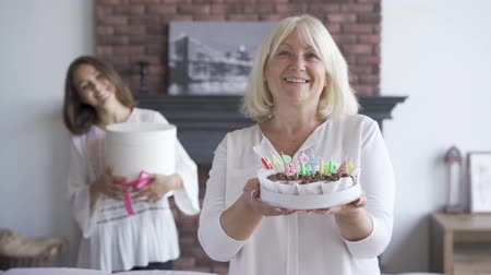 fire arms : Happy senior woman showing a cake to the camera. Smiling young woman standing with the present in the background Birthday celebration concept.