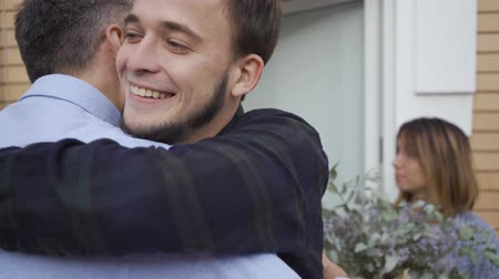 atender : Two caucasian men in the foreground greeting each other and smiling. Two attractive women in the backgroound talking and holding a cake and a flower bucket. Stock Footage