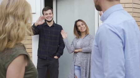 do widzenia : Married couple leaving home of they friends waving hands. Friendly neighbours visiting house of young man and woman. Concept of friendship, good relationship