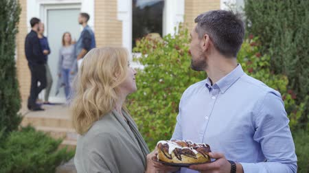 vecino : Happy mature couple with cake smiling and looking at camera standing in the foreground while company of people talking on the porch in the background. Meet new neighbors Archivo de Video