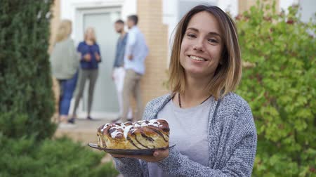 soglia : Young attractive woman with a cake smiling and looking at camera. Company of people talking on the porch in the background. Meet new neighbors.