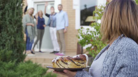 rassembler : Happy caucasian woman with cake smiling and looking at camera standing in the foreground while company of people talking and waving hands on the porch in the background. Meet new neighbors