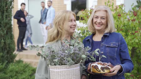 vecino : Two caucasian mature women smiling and holding a cake and a bucket of flowers. Company on the porch in the background waving to the camera.