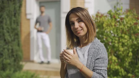 construct : Cute caucasian woman standing with the cup of tea in the foreground, her husband coming from behind and kissing her cheek. Young family together at the house. Summertime