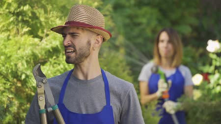 robes : Young modern farmer in blue robe standing in the foreground while his wife watering trees in the background. Male and female worker in the garden Stock Footage