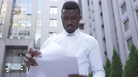 捨てる : Close-up of African American man in white shirt reading documents and throwing them away. Male businessman or manager tired and stressed. 動画素材