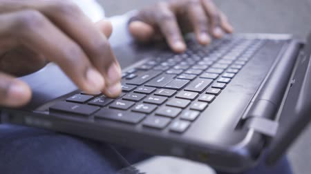werknemers : Close-up hands of African American man typing fast on the keyboard of his laptop. Confident male businessman or manager working outdoors Stockvideo