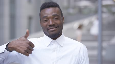 optimista : Close-up of smiling African American man in white shirt looking at camera with thumb up. Male businessman or manager satisfied with his work.