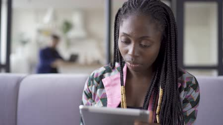 facecare : Young pretty African American woman with problem skin sitting at home working with her tablet. Leisure indoors. The girl resting after work. Gadget addiction