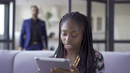 pigtailler : Young pretty African American woman with afro pigtails sitting at home working with her tablet. The girl calling her husband to show him picture. Leisure indoors Stok Video