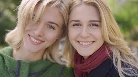 benzer : Portrait of two caucasian girlfriends looking at the camera smiling. Friendly relationship. Young women together outdoors