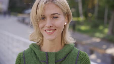 закрывать : Close-up face of young blond caucasian woman with short hair smiling happily looking at the camera in the city street. Emotions, happiness, good mood