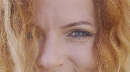 curly haired : Extreme close-up face of mature red-haired woman with curly hair smiling happily looking at camera. Natural beauty concept. Emotions, happiness, good mood Stock Footage