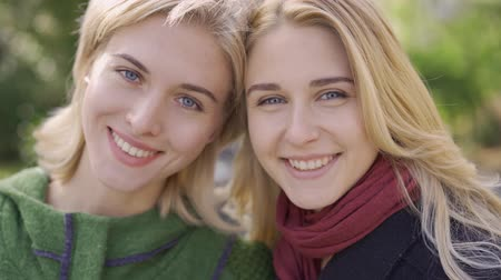 benzer : Two beautiful blond caucasian girls looking at camera and smiling. Friendly relationship. Young women spending time together outdoors.