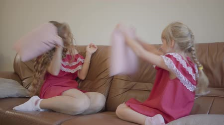 コミットメント : Happy blond caucasian mother and little daughter playing and hitting using a pillow at home. Concept of motherhood, childhood. Happy family.