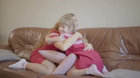 nutrir : Caucasian mother and daughter with blond hair dressed in red nighties hugging on the sofa at home. Happy family spendng evening night together.