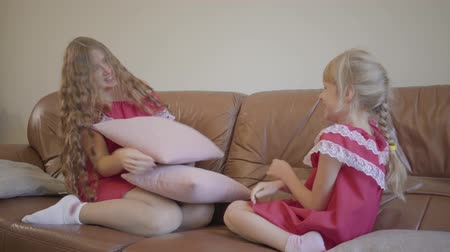 nutrir : Happy blond caucasian mother and little daughter in the same dresses playing at home, the girl hits mom with a pillow. Concept of motherhood, childhood, one parent. Happy family Stock Footage