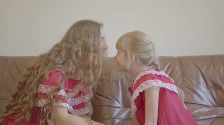 отпрыск : Happy blond caucasian mother and little daughter in same dresses touching noses and hugging at home. Concept of motherhood, childhood, one parent. Happy family