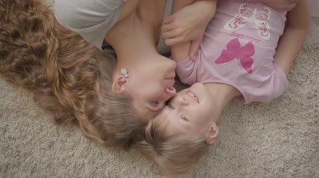 nutrir : Top view of happy caucasian mother and her little daughter laying on fluffy carpet at home. Woman and girl resting at home and smiling. Happy family. Stock Footage