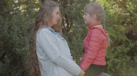 tegenhouden : Caucasian woman with long blonde hair palying with her little girl in the autumn park. Mother and daughter resting at weekends. Happy family, motherhood, childhood. Stockvideo