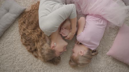 nurture : Top view of happy caucasian mother and her little daughter in red dress laying on fluffy carpet at home. Woman and girl resting at home and smiling. Happy family.