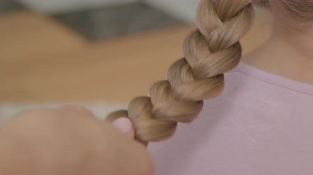 braids : Close-up hands of young woman braids a braid of her blond daughter. Concept of motherhood, childhood, one parent. Leisure indoors. Happy family Stock Footage
