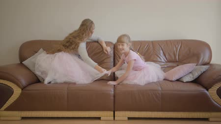 szerep : Happy caucasian mom and daughter in the same pink dresses jumping on the coach and turning the TV with a remote controller. Blonde woman and little cute girl spending evening night together.