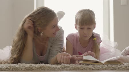 elkötelezettség : Carefree blond caucasian mother and little daughter laying on the bed. Pretty woman explaining contents of the book to the little girl. Child education.
