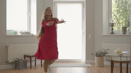 nurture : Blond caucasian mother and daughter in the same red dresses dancing at home holding hands. Concept of motherhood, childhood, one parent. Happy family spending day together. Stock Footage