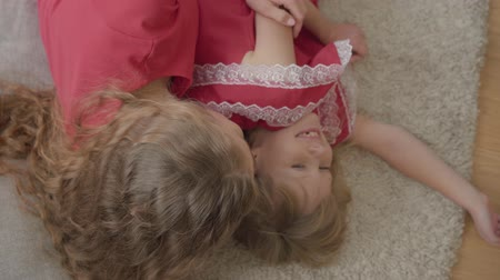 コミットメント : Top view of happy mother and her daughter in the same red dresses laying on the fluffy carpet. Woman and girl resting at home at weekends. Happy family. 動画素材
