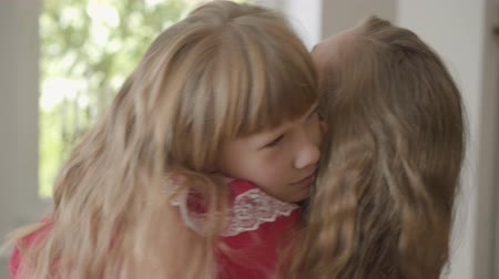 nutrir : Close-up of happy blond caucasian mother with long hair and little daughter hugging at home. Concept of motherhood, childhood, one parent. Leisure indoors. Happy family Stock Footage