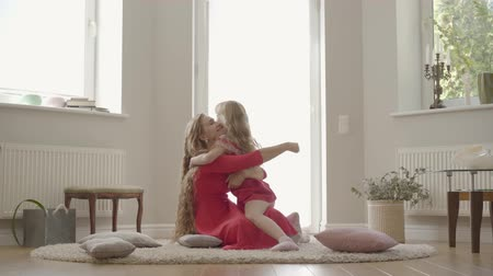 nutrir : Cute girl running to the attractive woman with long curly hair and hugging her. Young blond caucasian mother and her little pretty daughter laying on the floor on fluffy carpet.