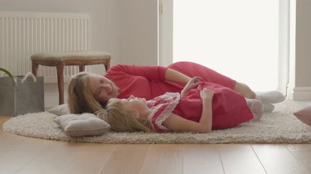 nutrir : Happy blond caucasian mother and little daughter talking while laying on the floor on fluffy carpet at home. Concept of motherhood, childhood, one parent. Happy family, tender relationship