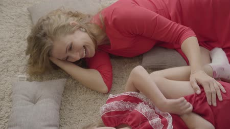 nutrir : Top view of beautiful young woman and little blond girl laying on the fluffy carpet and soft pillows. Caucasian mother and daughter in red dresses spending evening at home resting.