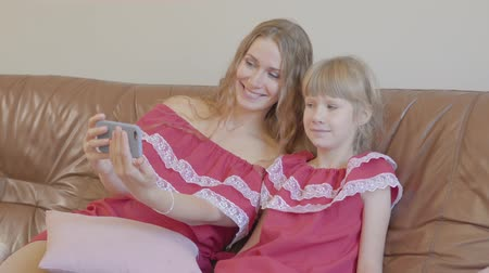 nutrir : Happy blond caucasian mother and little daughter in same dresses sitting on the couch taking selfie using cellphone at home. Concept of motherhood, childhood, one parent. Happy family
