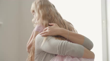 nurture : Little girl with long curly blond hair hugging attractive young caucasian woman. Daughter showing her love to the mother.