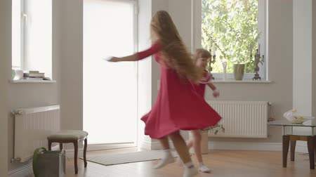отпрыск : Happy blond caucasian mother and little daughter in the same dresses playing at home, spinning around and dancing holding hands. Concept of motherhood, childhood, one parent. Happy family Стоковые видеозаписи