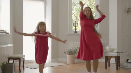 bond : Blond caucasian mother and daughter hacing fun at weekends. Beautiful woman and cheerful girl in the same red dresses dancing. Happy family spending day together. Stockvideo