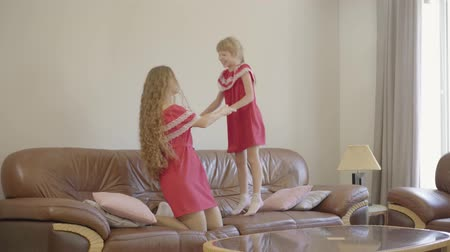 nutrir : Young pretty woman and little cute girl jumping on the brown coach with small soft pillows. Mother and daughter in red dresses spending time in the evening at home.