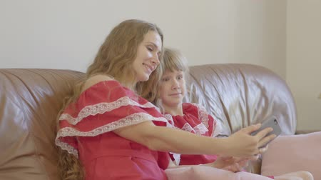 nutrir : Caucasian mother and little daughter in red dresses sitting on the couch taking selfie on the phone. Cheerful woman and funny girl making faces for a picture. Stock Footage