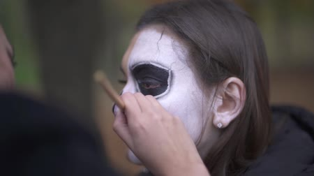 assombrada : Halloween. Makeup artist applies make-up to girl face Stock Footage