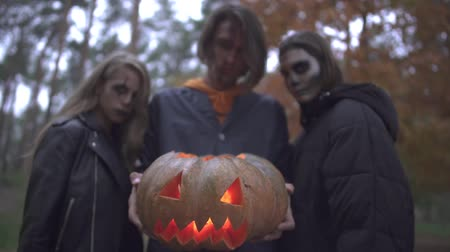 bıçaklar : Three caucasian friends with horrifying halloween make-up stand in the autumn park in the evening. Tall brunette guy holds a pumpkin with a candle inside. People looking into camera with evil looks. Stok Video