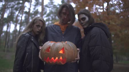 маска : Tall handsome man holding halloween pumpkin with a light inside, two pretty girls standing near. People with scary makeup on faces looking into camera with evil looks. Camera zooming. Bottom view